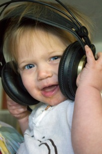 Baby with messy face wears headphone