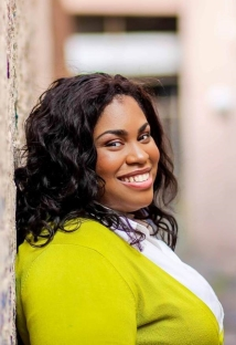 Angie Thomas, author of The Hate U Give, poses for an author photo. She stands sidewise on brick building in neon sweater and white shirt head towards the camera. Photo from www.lemuriabooks.com.