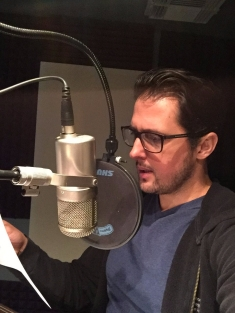 Writer and Narrator Pablo Cartaya reads in front of a microphone
